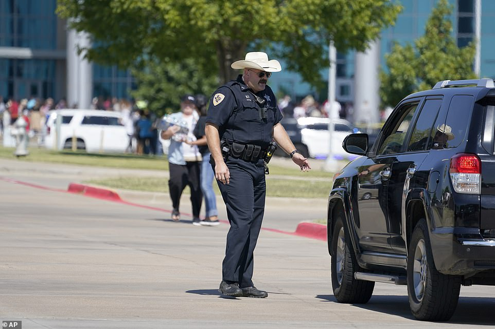 A law enforcement officer directs family members arriving at the Center For The Performing Arts to be reunited with their school children